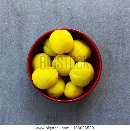 purified boiled yellow potatoes in a red bowl on a gray background closeup top view