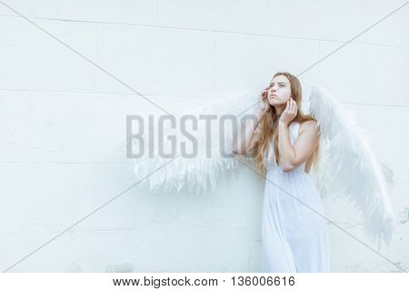 Beautiful angel girl with white wings near the wall. She looks up thoughtfully