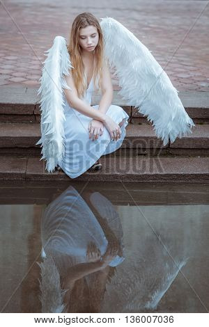 Portrait of a girl angel. She sits near the water and looks at she reflection