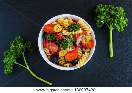 Salad: pasta fusilli black and green olives cherry tomatoes red onion and parsley. Dressing: olive oil and lemon juice. In white bowl. Black stone background. Top view.