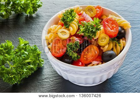 Salad: pasta fusilli black and green olives cherry tomatoes red onion and parsley. Dressing: olive oil and lemon juice. In white bowl. Black stone background.