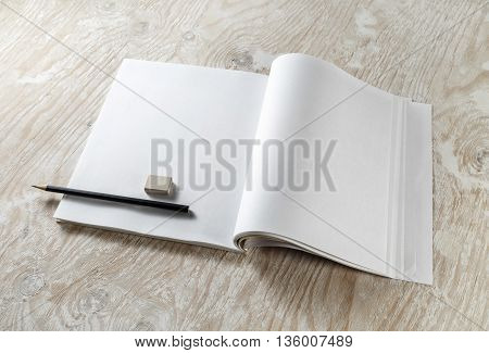 Blank opened brochure with a pencil and eraser with soft shadows on light wooden background. Blank Template for your design. Responsive design template.
