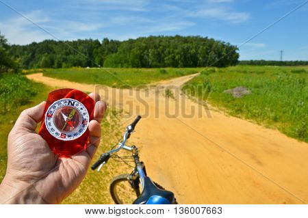 With the compass on a walk. Man's hand holds a magnetic compass.