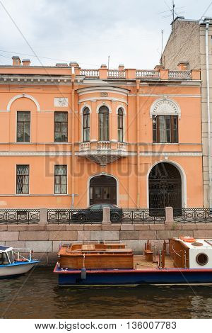 Orange classic house with a bay window and an arched gate on the Moika River.
