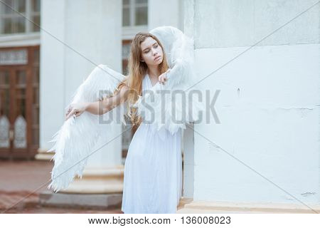 Young blonde girl with white angel wings