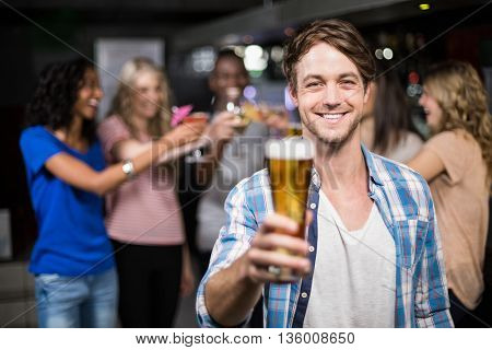 Smiling man showing a beer with his friends in a nightclub