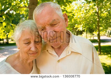 The sad old couple in the summer on a walk in park.
