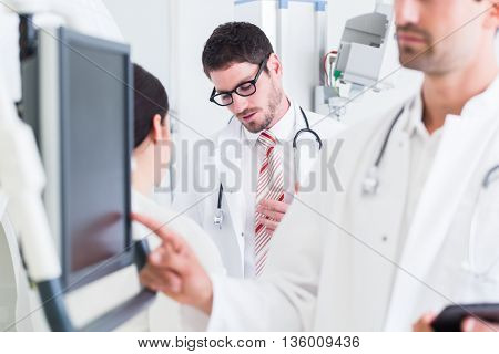Doctors discussing images of x-ray scan in CT