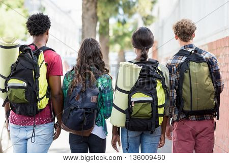 Rear view of friends standing with rucksack