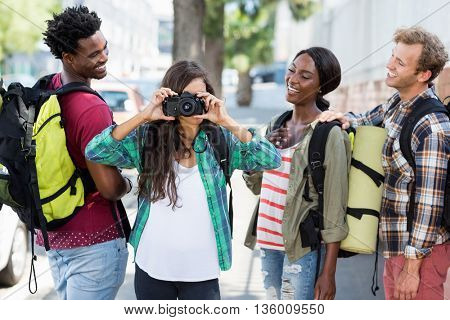 Woman taking photo while friends looking at her and smiling