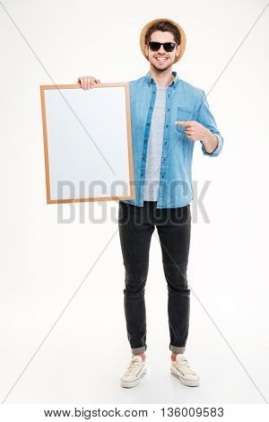 Happy handsome young man holding blank whiteboard and pointing on it over white background