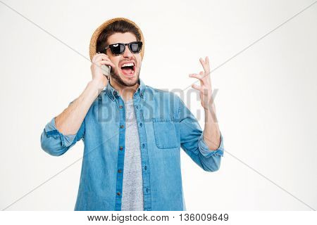 Happy excited young man in hat and sunglasses talking on cell phone over white background
