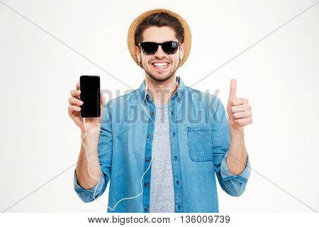 Cheerful young man in earphones showing blank screen cell phone and showing thumbs up over white background