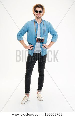 Full length of happy handsome young man with old vintage photo camera over white background