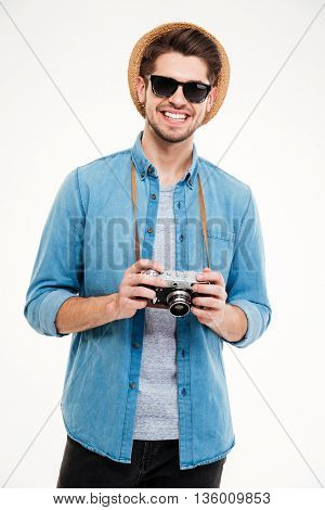 Closeup of happy atttractive young man in hat and sunglasses with old vintage photo camera over white background