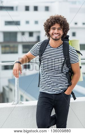 Portrait of happy young man wearing rucksack standing on terrace