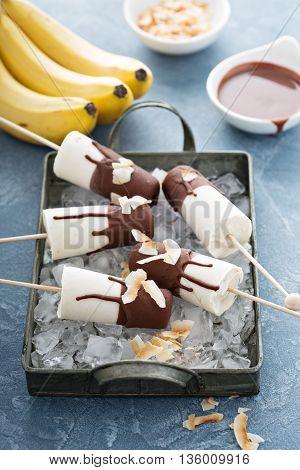 Banana and chocolate homemade ice cream popsicles with yogurt and coconut