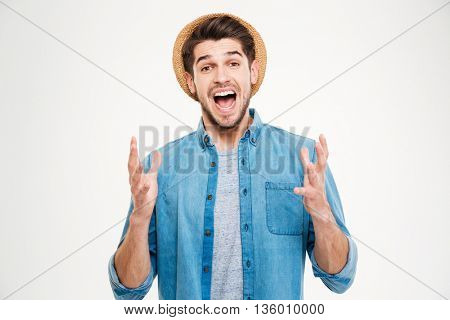 Happy excited young man celebrating success and shouting over white background