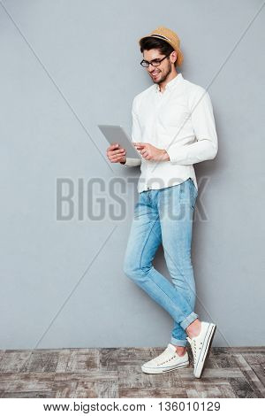Full length portrait of a happy young stylish man using tablet computer isolated on a gray background