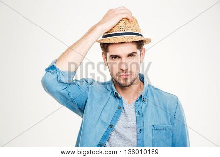 Portrait of attractive bristled young man in blue shirt and hat over white background