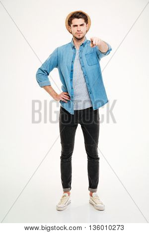 Full length of confident handsome young man standing and pointing on you over white background