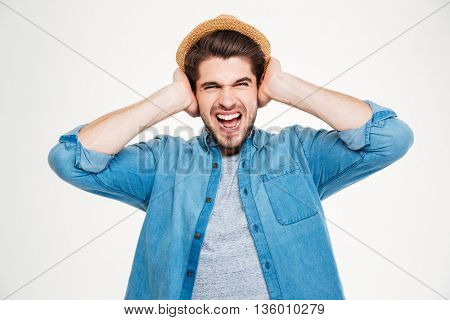 Mad irritated young man covered ears by hands and screaming over white background