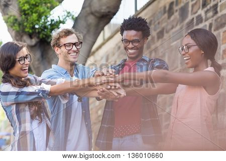 Happy friends putting their hands together
