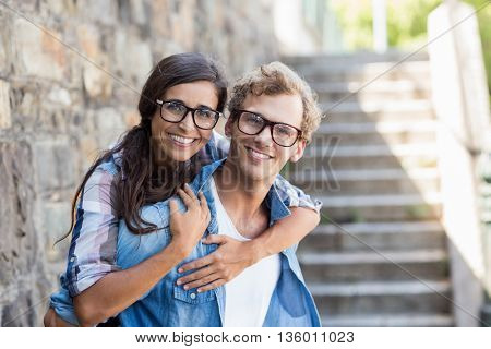 Portrait of young man giving piggyback to his woman