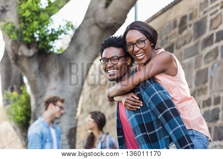 Portrait of young man giving piggyback to woman with friend background