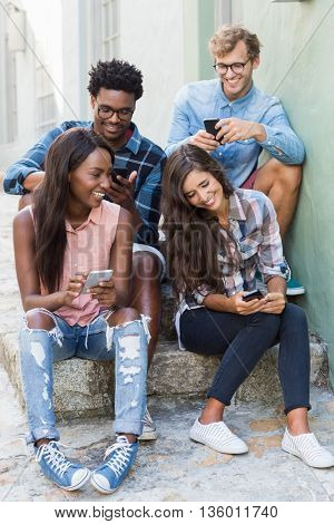 Group of friends sitting together using mobile phone