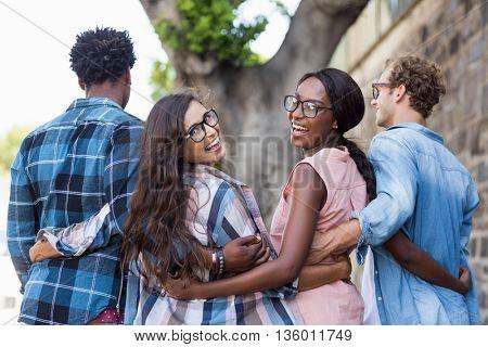 Women smiling at camera while walking with men