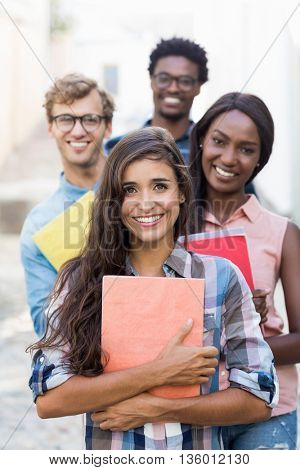 Portrait of happy friends holding book