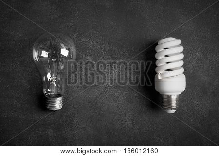 Electric bulbs on the black chalkboard (old and modern lamp)