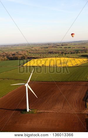 An aerial view of a modern windmill and hot air balloon in the background flying over an oilseed rape field in the English countryside