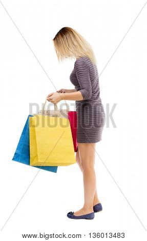 back view of woman with shopping bags. beautiful brunette girl in motion. backside view person. Rear view people collection. Isolated over white background. Girl in dress looking into shopping bags