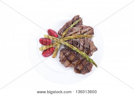grilled red beef pork meat bbq steak fillet with asparagus and hot pepper served on plate isolated on white background