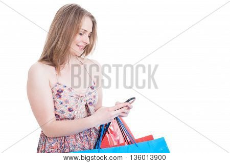 Happy Young Shopper With Gift Bags Texting On Cellphone