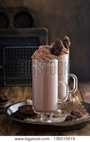 Chocolate cookie milkshake in tall mugs with chocolate whipped cream