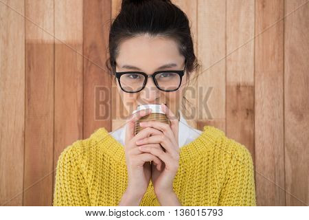 Hipster drinking coffee on wooden background