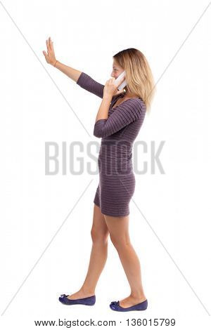 side view of woman walking with a mobile phone.  backside view of person.  Rear view people collection.  Girl in a short dress is talking to the right on the white smartphone and someone waving  hand.