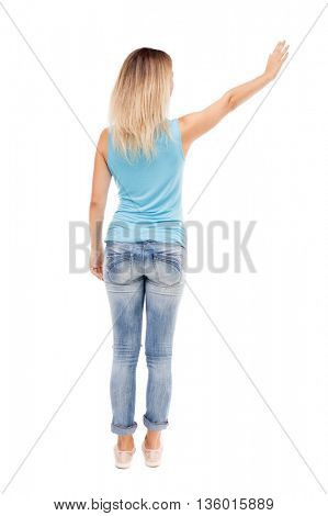 Back view of beautiful woman welcomes. Young teenager girl in jeans hand waving from. Rear view people collection. Isolated over white background. girl in jeans and shirt with his left hand waving