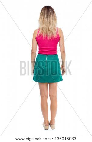back view of standing young beautiful  woman.  girl  watching. Rear view people collection.  backside view of person.  The blonde in a green skirt and pink blouse stands and looks forward.