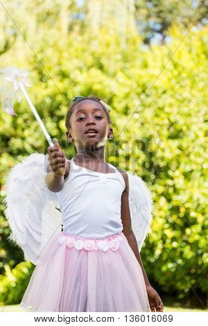 Cute mixed-race girl wearing a fairy dress and pointing the camera with her magic wand on a park