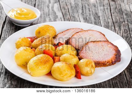 Oven Baked new potatoes with sea salt red bell pepper and pork tenderloin cutting into slices on a white dish with sauce in a gravy boat on a wooden background close-up view from above