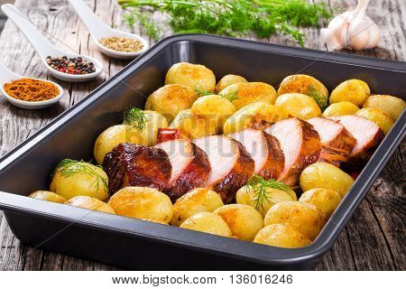 Oven Baked new potatoes with sea salt red bell pepper and pork tenderloin cutting into pieces in a baking dish spices in a porcelain spoons on a wooden background close-up view from above