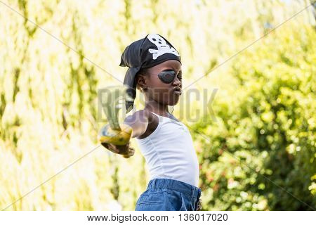 Cute mixed-race girl grimacing and wearing pirate clothes on a park
