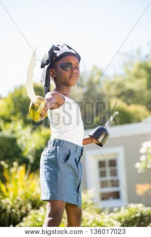 Cute mixed-race girl wearing pirate clothes and pointing the camera with plastic sword on a park