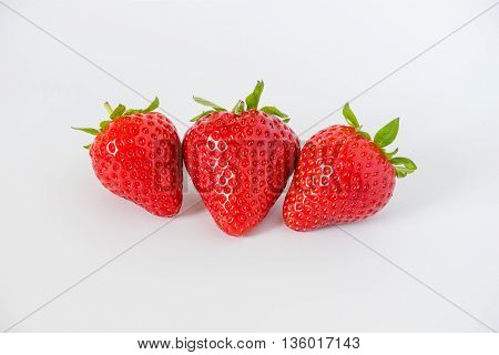 Cluster of ripe red whole fresh strawberries with green stalks and flower buds on a light grey background with.
