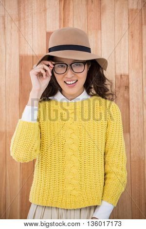 Hipster with hat and glasses on wooden background