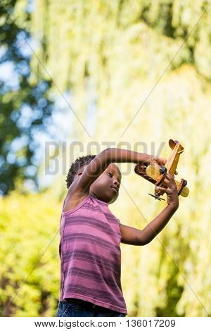 Cute mixed-race boy playing with a little plane on a park